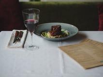 Μια σύνθεση γευμάτων σε ένα άσπρο τραπεζομάντιλο Ένα πιάτο με το πιάτο κρέατος, μια υπηρεσία γευμάτων και ένα ποτήρι του κρασιού  Στοκ Εικόνες