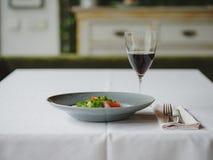Μια σύνθεση γευμάτων σε ένα θολωμένο υπόβαθρο εστιατορίων Ένα νόστιμο πιάτο δίπλα σε ένα ποτήρι του κόκκινου κρασιού διάστημα αντ Στοκ Φωτογραφία