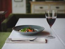 Μια σύνθεση γευμάτων σε ένα θολωμένο υπόβαθρο εστιατορίων Ένα νόστιμο πιάτο δίπλα σε ένα ποτήρι του κόκκινου κρασιού διάστημα αντ Στοκ εικόνα με δικαίωμα ελεύθερης χρήσης