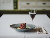 Μια σύνθεση γευμάτων σε ένα θολωμένο υπόβαθρο εστιατορίων Ένα νόστιμο πιάτο δίπλα σε ένα ποτήρι του κόκκινου κρασιού διάστημα αντ Στοκ φωτογραφίες με δικαίωμα ελεύθερης χρήσης