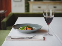 Μια σύνθεση γευμάτων σε ένα θολωμένο υπόβαθρο εστιατορίων Ένα νόστιμο πιάτο δίπλα σε ένα ποτήρι του κόκκινου κρασιού διάστημα αντ Στοκ Εικόνες