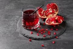 Μια σύνθεση ενός ποτού ροδιών και η περικοπή garnet σε ένα σκούρο γκρι υπόβαθρο Υγιεινός, φυσικός, φρέσκος κόκκινος χυμός στοκ εικόνα