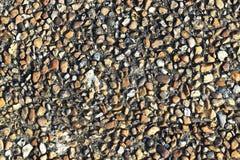 Μια σύσταση του αμμοχάλικου σε ένα γκρίζο υπόβαθρο ως υπόβαθρο Στοκ φωτογραφίες με δικαίωμα ελεύθερης χρήσης