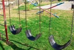 Μια ταλάντευση φιαγμένη από ρόδες στο χορτοτάπητα playground στοκ εικόνα