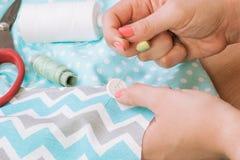 Μια τη φωτογραφία το seamstress ` s των χεριών κατά λειτουργία με το ύφασμα υφάσματος στοκ εικόνες με δικαίωμα ελεύθερης χρήσης