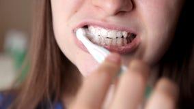 Μια τοποθέτηση νέων κοριτσιών μπροστά από τη κάμερα βουρτσίζει τα δόντια της υγιή δόντια φιλμ μικρού μήκους