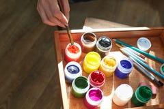 Μια τοπ άποψη των αντικειμένων για το σχέδιο Βούρτσες, χρώματα σε ένα κιβώτιο για τα υλικά στο ξύλινο παρκέ τέχνης ανασκόπησης μα Στοκ Εικόνες