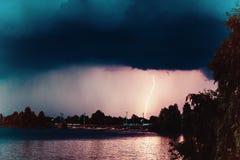 Μια τροπική θύελλα βροντής πέρα από μια πόλη χωρών με την απεργία αστραπής Στοκ εικόνα με δικαίωμα ελεύθερης χρήσης