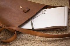 Μια τσάντα δέρματος με ένα λεύκωμα για το σχέδιο και ένα μολύβι στοκ εικόνες