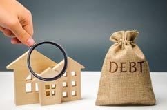 Μια τσάντα των χρημάτων με το χρέος λέξης και τα ξύλινα σπίτια Η έννοια του χρέους για την κατοικία Υποθήκη Ακίνητη περιουσία, εγ στοκ εικόνες