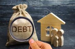 Μια τσάντα των χρημάτων με το χρέος λέξης και την οικογένεια που στέκονται κοντά στο σπίτι Η έννοια του χρέους για την κατοικία Υ στοκ φωτογραφία με δικαίωμα ελεύθερης χρήσης