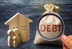 Μια τσάντα των χρημάτων με το χρέος λέξης και την οικογένεια που στέκονται κοντά στο σπίτι Η έννοια του χρέους για την κατοικία Υ στοκ εικόνα με δικαίωμα ελεύθερης χρήσης