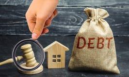 Μια τσάντα των χρημάτων με το χρέος, το σπίτι και gavel λέξης Η έννοια του χρέους για την κατοικία Υποθήκη Ακίνητη περιουσία, ένν στοκ εικόνα