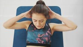 Μια υγιής γυναίκα που κάνει τη σωματική άσκηση με τον αθλητικό ιματισμό και που εκπαιδεύει στο σπίτι Υγιής τρόπος ζωής