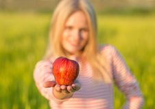 Μια υγιής ελκυστική γυναίκα που ένα κόκκινο μήλο πράσινο καλοκαίρι πεδίων στοκ φωτογραφία