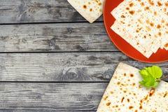 Μια υπερυψωμένη φωτογραφία του εβραϊκού ψωμιού Matzah στο κεραμικό πιάτο στον πίνακα grunge Το Matzah και η άνοιξη ο κλάδος δέντρ Στοκ φωτογραφία με δικαίωμα ελεύθερης χρήσης