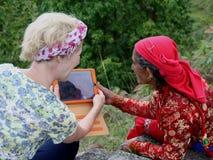 Μια δυτική γυναίκα παρουσιάζει ηλικιωμένες ασιατικές γυναίκες μια ταμπλέτα Στοκ Εικόνες