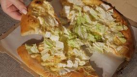 Μια φέτα της πίτσας στο χέρι του φιλμ μικρού μήκους