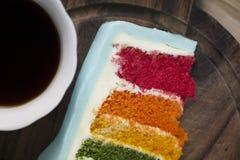 Μια φέτα του κέικ ουράνιων τόξων με ένα φλιτζάνι του καφέ στοκ εικόνα