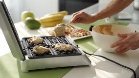 Μια φίλαθλη γυναίκα που μαγειρεύει τις εύγευστες βελγικές βάφλες βακκινίων για το πρόγευμα το πρωί στην κουζίνα φιλμ μικρού μήκους