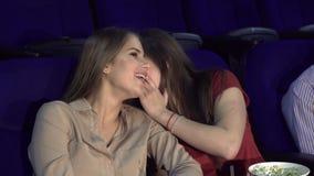 Μια φίλη ψιθυρίζει κάτι σε ένα δεύτερο κορίτσι προσέχοντας έναν κινηματογράφο απόθεμα βίντεο