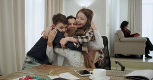 Μια φιλική σχέση μεταξύ μητέρας και τριών παιδιών της αυτοί που αγκαλιάζουν ο ένας τον άλλον πολύ καλός σε ένα σύγχρονο σπίτι, εν απόθεμα βίντεο