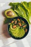 Μια φρέσκια και εύγευστη νόστιμη υγιής σαλάτα με το αβοκάντο και μύδια στο άσπρο υπόβαθρο στο μαύρο κύπελλο στοκ εικόνα