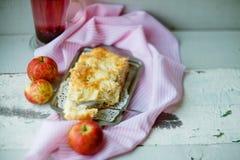 Μια φρέσκια ψημένη πίτα μήλων και ένα κομμάτι περικοπών της πίτας ψεκάζονται με την κονιοποιημένη ζάχαρη, άποψη κινηματογραφήσεων Στοκ Εικόνες