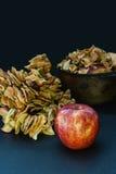 Μια φρέσκια Apple είναι στο υπόβαθρο των ξηρών μήλων στη δέσμη και σε ένα εμπορευματοκιβώτιο μετάλλων Στοκ Φωτογραφίες