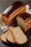 Μια φραντζόλα του ψωμιού σίκαλη-σίτου με τις φέτες στοκ εικόνα