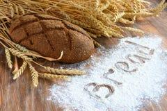 Μια φραντζόλα των αυτιών ψωμιού και σίτου στο ξύλινο υπόβαθρο με το αλεύρι Στοκ Φωτογραφία