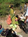 Μια φυλετική γυναίκα πωλεί τα φρέσκα λαχανικά Στοκ Εικόνα