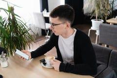 Μια φωτογραφία ενός όμορφου ατόμου που φορά τα γυαλιά που εξετάζουν την οθόνη ενός κινητού τηλεφώνου Ο τύπος κάθεται στον πίνακα στοκ εικόνες με δικαίωμα ελεύθερης χρήσης