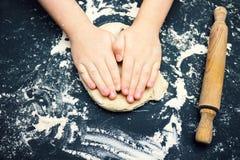 Μια φωτογραφία των χεριών παιδιών με τον κόπτη που κατασκευάζει τη σπιτική παραδοσιακή καρδιά να διαμορφώσει τα μπισκότα Χριστουγ Στοκ Φωτογραφία