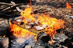 Μια φλόγα μπριζόλας μπριζολών χοιρινού κρέατος που ψήνεται σε μια σχάρα Στοκ Εικόνες