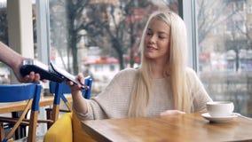 Μια χαμογελώντας νέα γυναίκα κάνει μια ανέπαφη πληρωμή σε έναν πίνακα καφέδων απόθεμα βίντεο