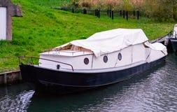 Μια χαρακτηριστική ολλανδική βάρκα ελλιμένισε σε μια ακτή με τη χλόη και κάλυψε επάνω από έναν άσπρο καμβά στοκ εικόνες