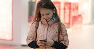 Μια χαριτωμένη μαθήτρια κρατά ένα κινητό τηλέφωνο στα χέρια της και κάνει τις σε απευθείας σύνδεση αγορές φιλμ μικρού μήκους