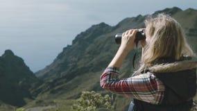 Μια χαριτωμένη ξανθή γυναίκα με τις διόπτρες πάνω από ένα βουνό απολαμβάνει μια περιβάλλουσα ομορφιά απόθεμα βίντεο
