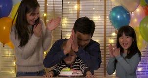 Μια χαριτωμένη συνεδρίαση μικρών παιδιών στον πίνακα και τα φυσώντας κεριά στα γενέθλια συσσωματώνουν σε σε αργή κίνηση απόθεμα βίντεο