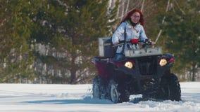 Μια χειμερινή δασική Α γυναίκα με την τρίχα πιπεροριζών που οδηγά το μεγάλο κόκκινο όχημα για το χιόνι απόθεμα βίντεο