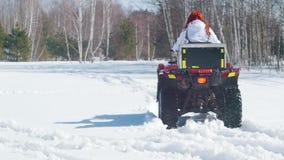 Μια χειμερινή δασική Α γυναίκα με το όχημα για το χιόνι οδήγησης τρίχας πιπεροριζών και υπερνίκηση του χιονιού φιλμ μικρού μήκους