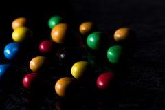 Μια χούφτα της ζωηρόχρωμης, στρογγυλής καραμέλας σοκολάτας στο Μαύρο και silv Στοκ Εικόνες