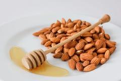 Μια χούφτα των αμυγδάλων σε ένα πιάτο με το μέλι και το μέλι μετακινούν με το κουτάλι σε ένα άσπρο υπόβαθρο Στοκ Εικόνα