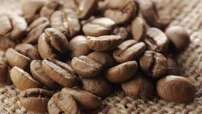 Μια χούφτα των καφετιών, ψημένων φασολιών καφέ burlap στο υπόβαθρο απόλυσης, κλείνει επάνω, περιστροφή φιλμ μικρού μήκους