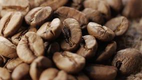 Μια χούφτα των καφετιών, ψημένων φασολιών καφέ burlap στο υπόβαθρο απόλυσης, κλείνει επάνω, περιστροφή απόθεμα βίντεο