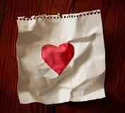 μια χρωματισμένη κόκκινη καρδιά εγγράφου σε ένα ξύλινο πάτωμα Στοκ Εικόνες