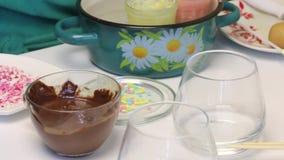 Μια χρωματισμένη popcake σάλτσα είναι στα πιάτα, και τα γυαλιά με την τήξη στέκονται στον πίνακα δίπλα σε την Στο πιάτο είναι σφα φιλμ μικρού μήκους