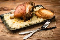 Μια ψημένη άρθρωση χοιρινού κρέατος εξυπηρέτησε με sauerkraut στο ξύλινο αγροτικό υπόβαθρο Στοκ Εικόνες