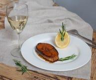 Μια λωρίδα του ατλαντικού σολομού, με το λεμόνι, το δεντρολίβανο και το ποτήρι του άσπρου κρασιού σε έναν ξύλινο πίνακα Στοκ Εικόνα